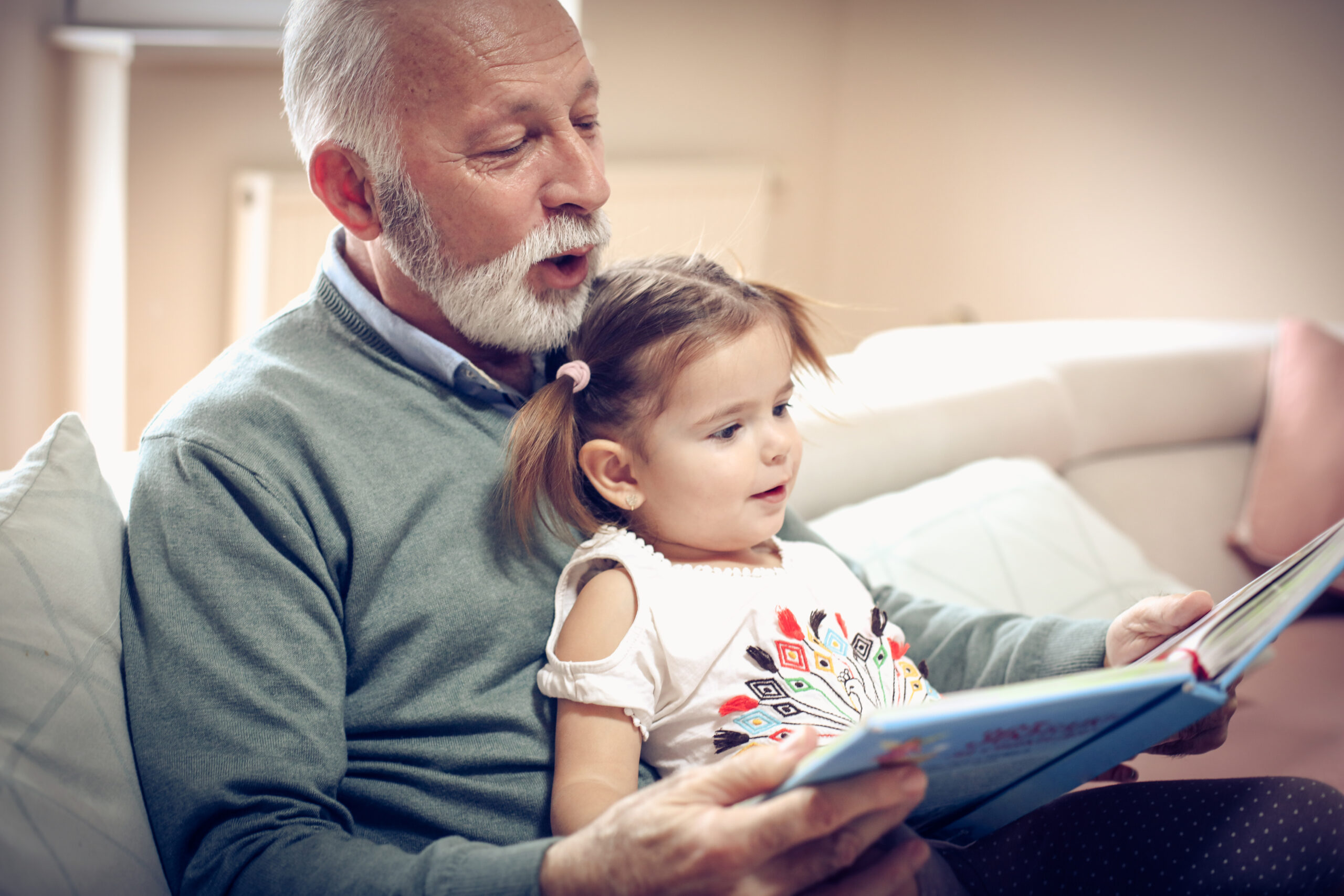 Happy grandfather and granddaughter reading book together at home. Close up.